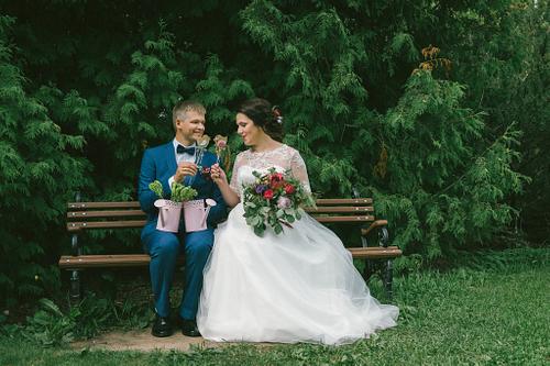 Līgava un līgavainis sēž uz soliņa