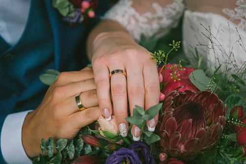 Kāzu gredzeni uz līgavas pušķa ziediem