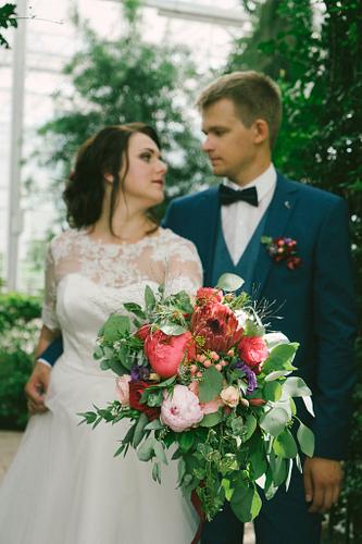Līgavas pušķis jaunais pāris fonā Salaspils Botāniskā dārza Oranžērijā