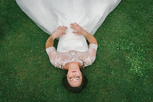 Līgava guļ zālē fotogrāfēts no augšas