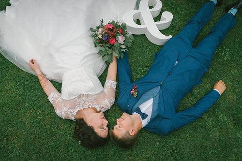 Līgava un līgavainis guļ zālē skats no augšas