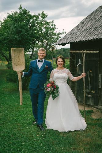 Līgava un līgavainis ar senajiem darba rīkiem pie pirtiņas