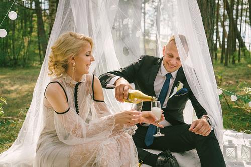Jaunais pāris atver šampanieti priežu mežā kāzu dekorācijas