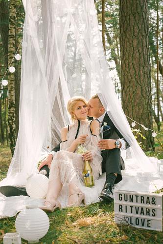 sieva vīrs dzer šampanieti zem balta baldahīna mežā kāzas