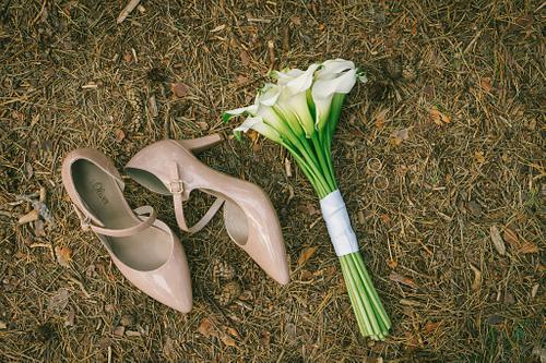 Līgavas pušķis un gredzeni baltas kallas līgavas kurpes priežu skujās