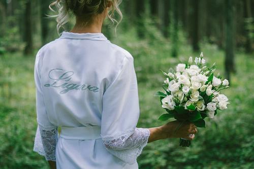Balts līgavas halāts ar uzrakstu Līgava rokās līgavas pušķis