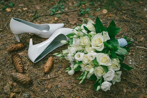 Baltas augstpapēžu kurpes un baltu rožu līgavas pušķis zemē