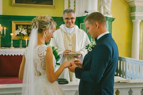 Kāzu ceremonija līgavainis velk gredzenu līgavas pirkstā pie altāra