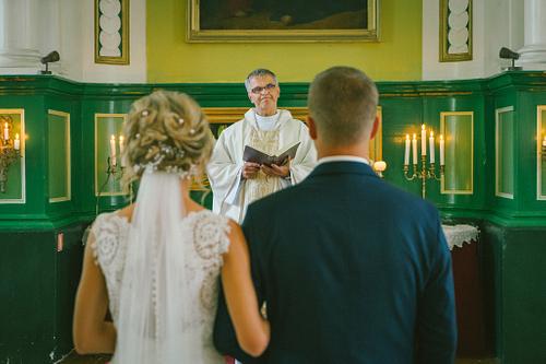 Jaunais pāris un mācītājs pie altāra baznīcā ceremonijas laikā