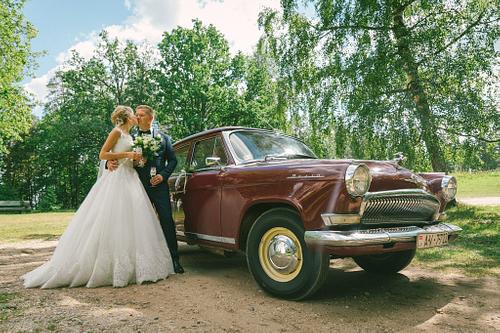 Jaunais pāris pie kāzu auto retro volga kāzās