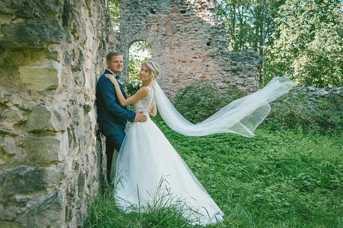 Kāzu fotosesija pilsdrupās līgavas plīvurs lido