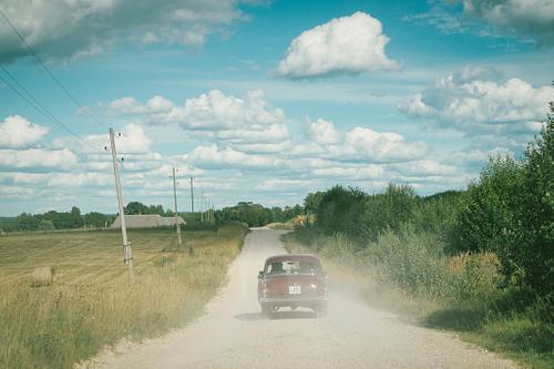 Kāzu auto volga brauc pa zemes ceļu saulainā vasaras dienā putekļi