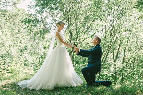Līgavainis uz viena ceļa nometies tur līgavas rokas