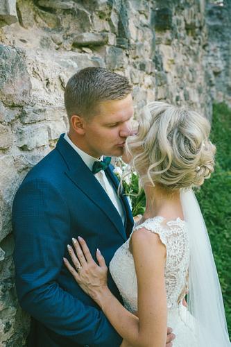 Līgava un līgavainis atspiedušīes pie pils mūra skūpstās