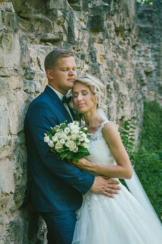 Līgava un līgavainis sapņaini pievērtām acīm pilsdrupās kāzu fotosesijā
