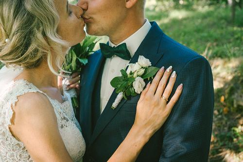 Laulību gredzens līgavas pirkstā uz līgavaiņa pleca