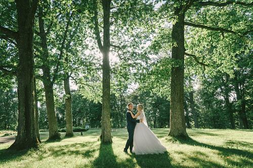Jaunā sieva un vīrs dejo saulainā ozolu parkā