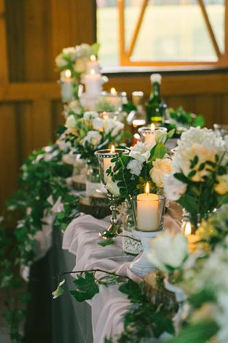 Kāzu mielasta galds rotāts ar baltām svecēm un ziedu virtenēm