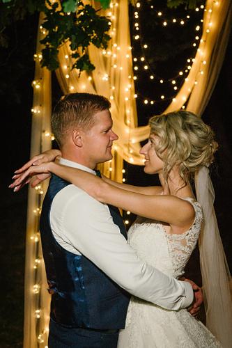 Jaunā sieva un vīrs mičošanas vietā ar lampiņām fonā