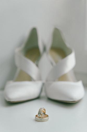 Līgavas kurpes fonā laulību gredzeniem