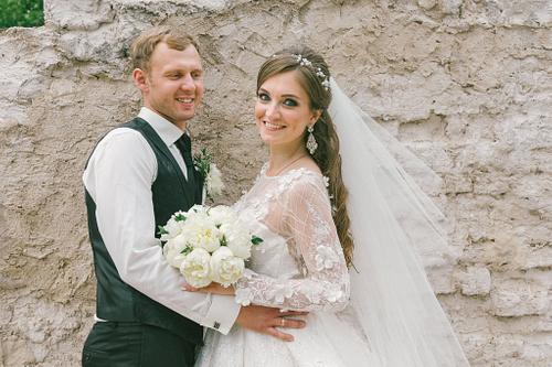Līgava un līgavainis pie dekoratīvas mūra sienas