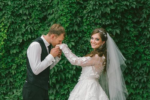Līgavainis skūpsta līgavas roku pie mežvīteņu sienas