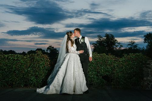 Jaunā sieva un vīrs saulrieta fotosesijā zem tumši zilām debesīm zibspuldzes gaismā