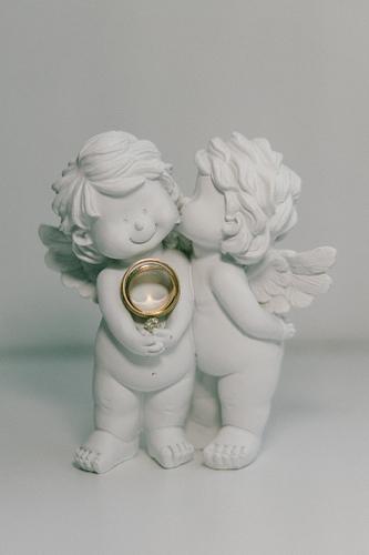 Laulību gredzeni uzlikti keramisku enģelīšu rokās