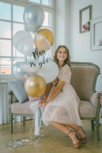 Meitene gaišā kleitiņā sēž uz smalka senlaicīga dīvāna ar hēlija baloniem rokās fonā liels logs baltā studijā