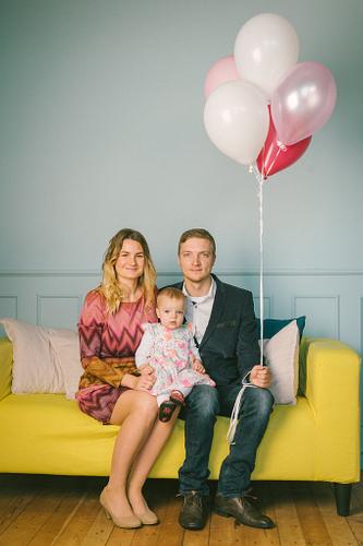 Ģimene sēž uz dzeltena dīvāna fotostudijā ar hēlija baloniem rokās fonā zila siena