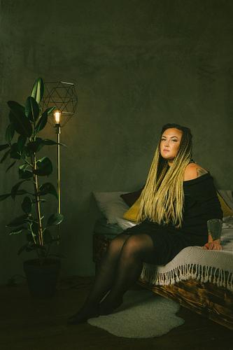 Sieviete uz gultas fotostudijā mājas istabas interjerā ar augiem puķu podos