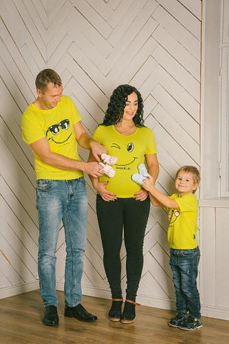 Ģimene dzeltenos krekliņos gaidību fotosesijā liek zīdaiņa čībiņas pie mammas punča