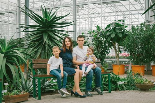 Ģimenes foto Botāniskajā dārzā sēžot uz soliņa starp kaktusiem džinsās un baltos kreklos