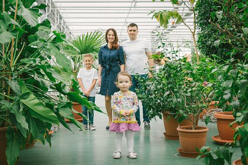 Ģimenes foto Botāniskajā dārzā bērns priekšplānā vecāki fonā starp lielām puķēm