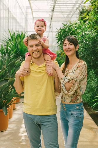 Ģimenes portrets Botāniskajā dārzā, bērns sēž tētim uz pleciem