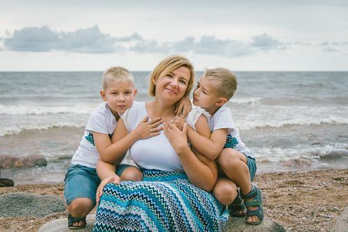Mamma un dēli fotosesijā pie jūras saskaņotos tērpos