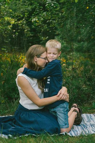 Mamma apskauj dēlu ģimenes fotosesijā vasarā sēžot uz segas