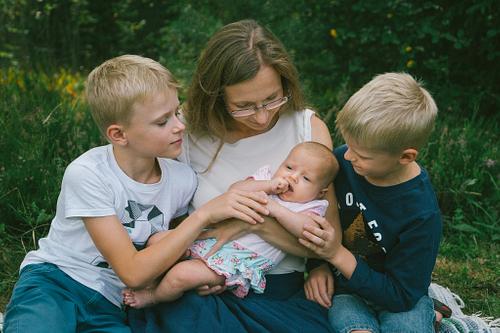 Ģimenes foto mamma un bērni apskāvuši mazuli
