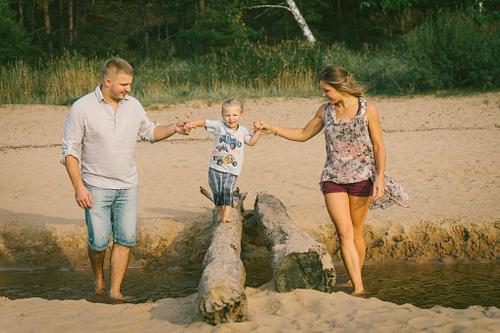 upes ieteika jūras pludmalē vecāki tur bērnu ejot pa tiltiņu ģimenes fotosesija