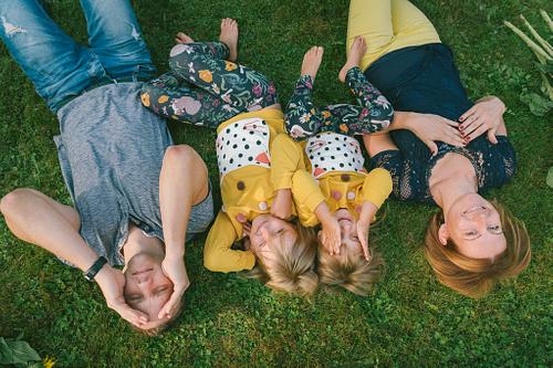 Ģimenes bilde guļot zālē vecāki un divas meitas dzeltenos džemperos