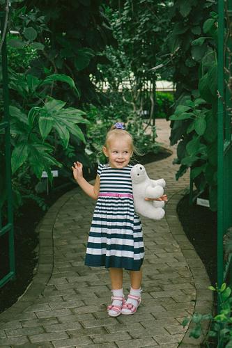 Meitene svītrainā kleitiņā Botāniskajā dārzā bērna fotosesijā