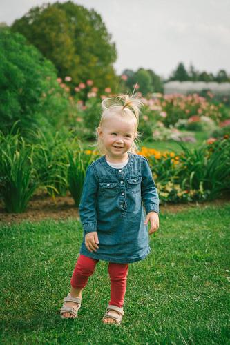 Meitenīte zilā kleitā un sarkanos legingos bērnu fotosesija vasarā starp puķu dobēm