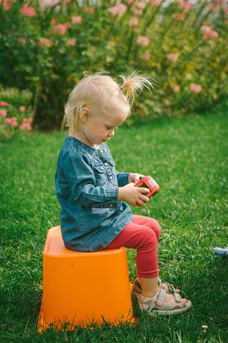 Meitenīte sēž uz plastmasas rotaļu kastes zālē džinsu kleita ar legingiem bērnu fotosesijā