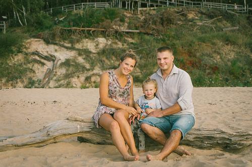 Ģimenes portrets sēžot jūrmalā uz koka baļķa smiltīs Saulkrastos