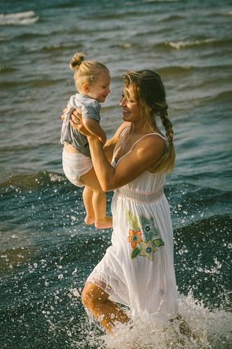 Mamma nes mazuli cauri ūdens šļakatām vasaras fotosesija jūrā ģimenes bērna fotosesija