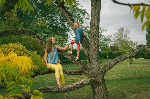 Mamma un meita sēž koka zaros rudenīga dzeltenu lapu fotosesija