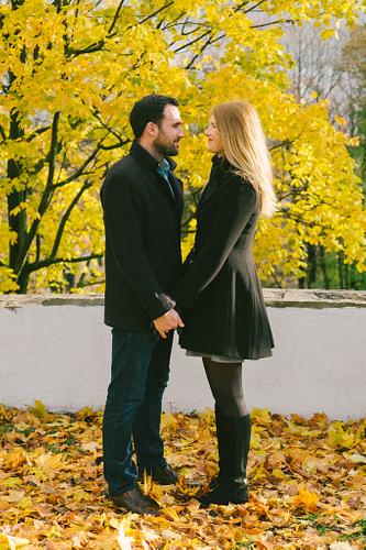 spilgti dzeltenas kļavas lapas rudens fotosesija pārim melnās drēbēs