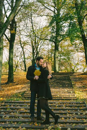 rudens lapas parkā pāris stāv uz trepēm fotosesijā