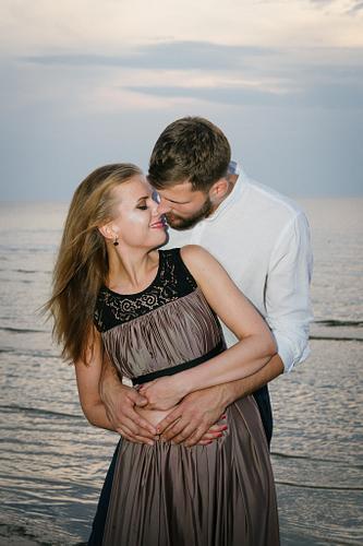 Pāris apskāvies fonā jūra saulrieta laikā fotosesija pārim