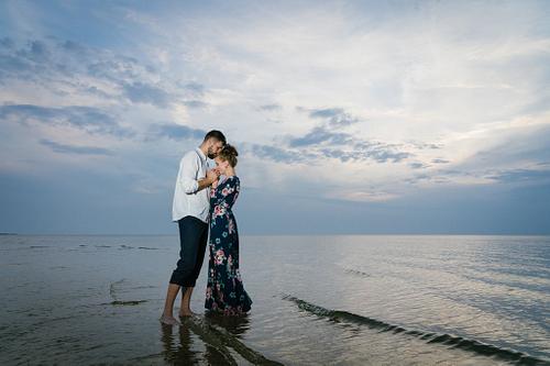 Romantisks pāris saulrietā stāv jūrā ūdenī ar pierēm kopā fotosesijā